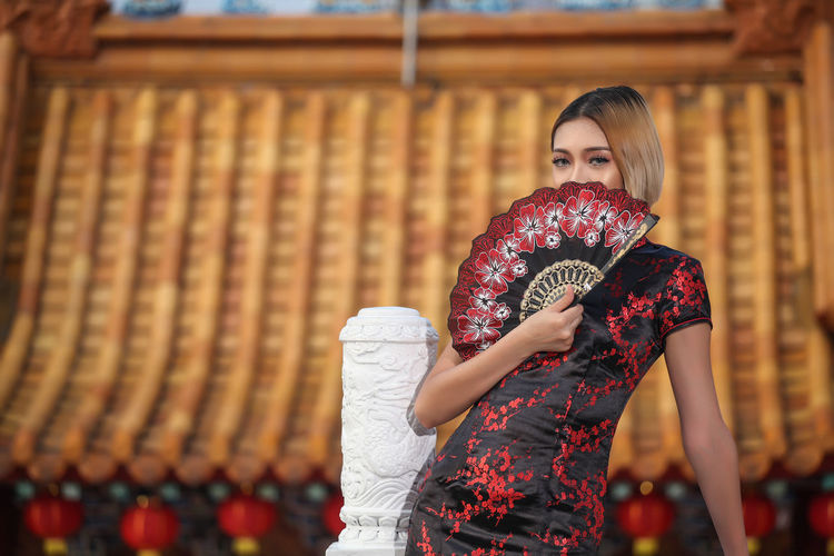 Portrait of woman holding folding fan while standing on building terrace