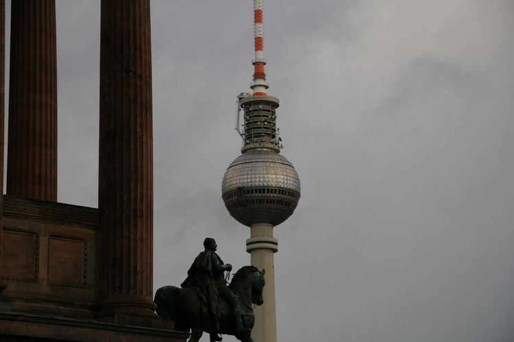 Low angle view of statue against modern buildings in city