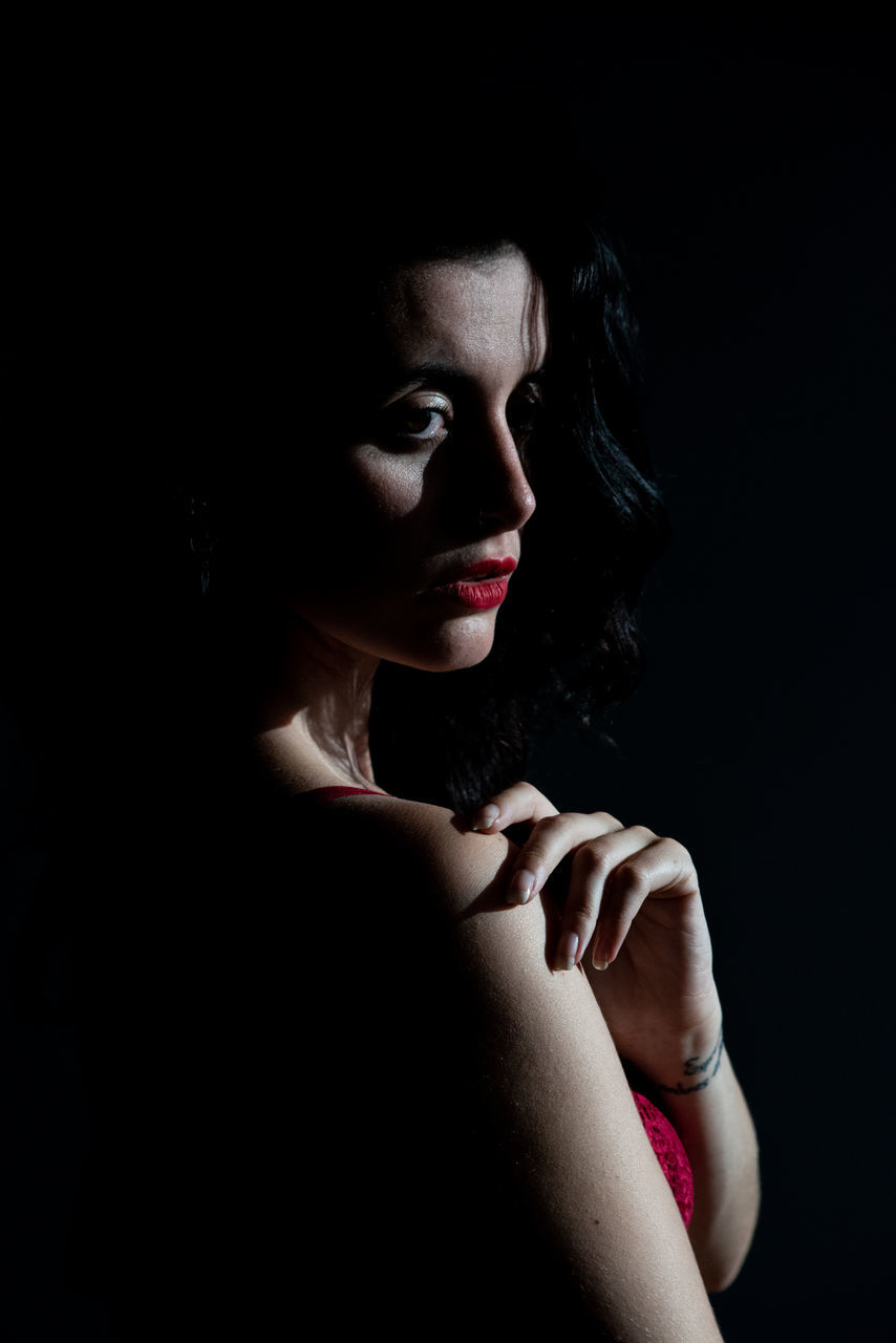 black background, one person, studio shot, young adult, indoors, headshot, women, portrait, lipstick, beauty, lifestyles, young women, make-up, beautiful woman, front view, close-up, adult, real people, dark, contemplation