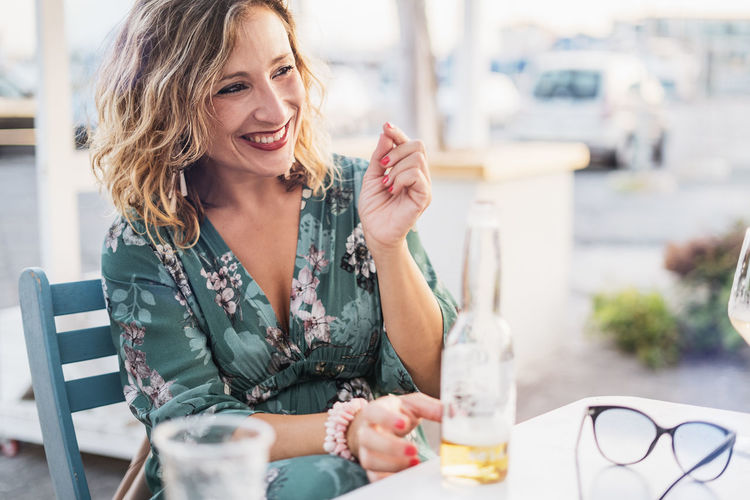 Happy Woman Having Beer While Sitting At Outdoor Restaurant