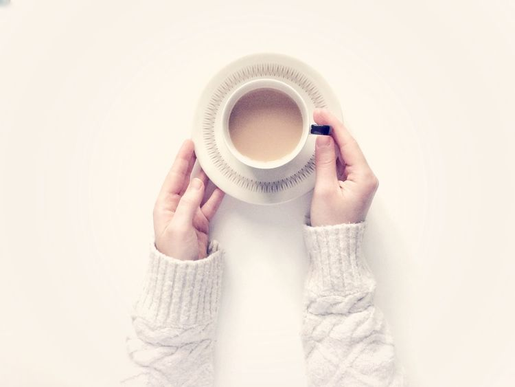 Looking down onto a white background with a girl's hands holding a cup of tea in a cup and saucer. Copy Space Cosy Jumpers Clean Contemporary Modern White Hands Girl Cosy From Above  Aerial View Lifestyle Cup And Saucer Cup Of Tea Human Hand One Person Holding Human Body Part Coffee Cup Drink Food And Drink Women Warm Clothing Indoors