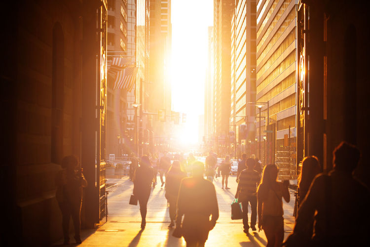 People on street amidst buildings in city during sunset