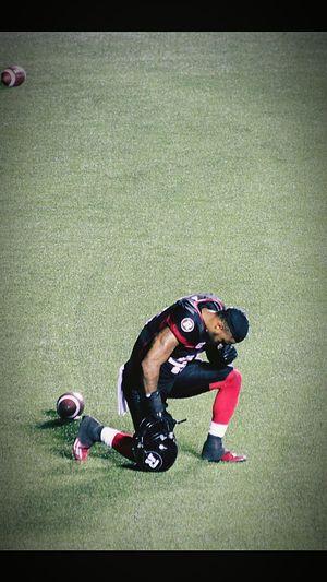 Ottawa Redblacks player praying to the fooball gods before game time.