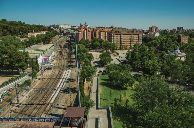 Train station with long rails among apartment buildings and wooden gardens, in madrid, spain.