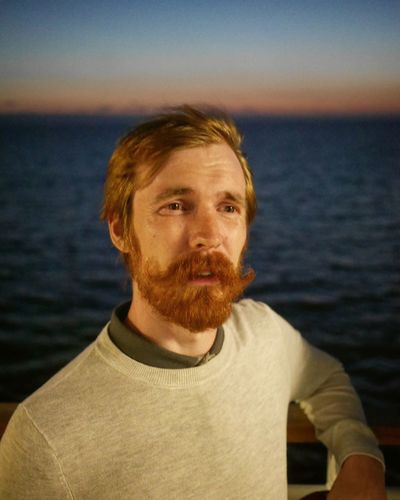 Portrait of man against sea during sunset