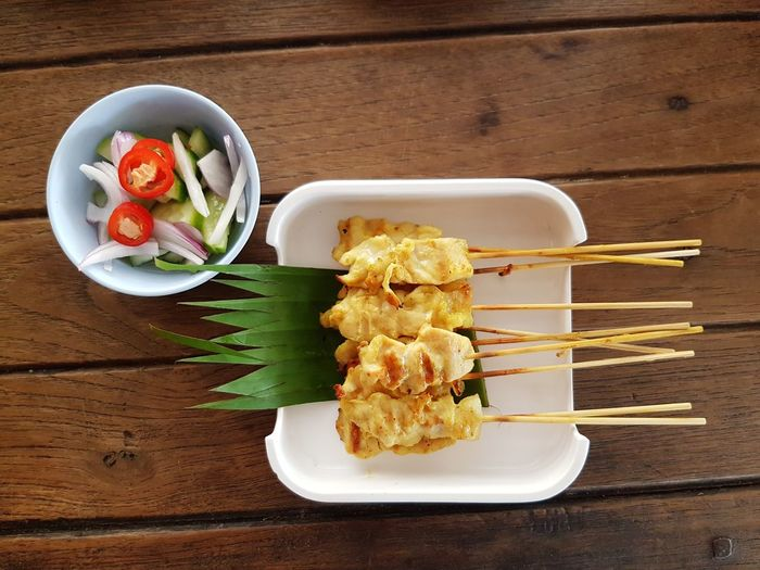 Top view of pork satay in white dish on the wooden table Top View Food And Drink Served Pork Satay Grilled Comfort Food Plate Directly Above Table Wood - Material Close-up Food And Drink Serving Dish Deep Fried  Starter Appetizer