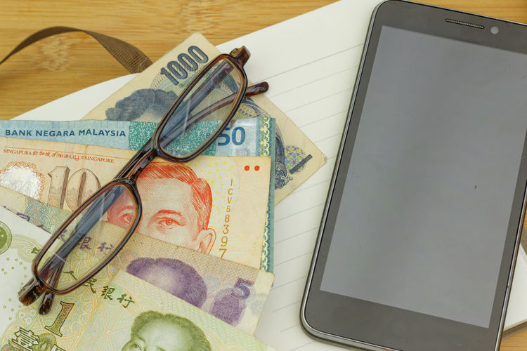 Blank smartphone screen with international currency and eyeglasses Concept Conceptual Smart Phone Phone Copyspace Copy Space Money Eyeglasses  Business Finance And Industry High Angle View Sunglasses Close-up Reading Glasses Eyewear Money Currency