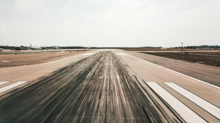 Runway Runway Sky Nature Day Diminishing Perspective Land Clear Sky Scenics - Nature Horizon Beauty In Nature Transportation Copy Space No People Landscape Outdoors Environment Tire Track Tranquility vanishing point Tranquil Scene Field