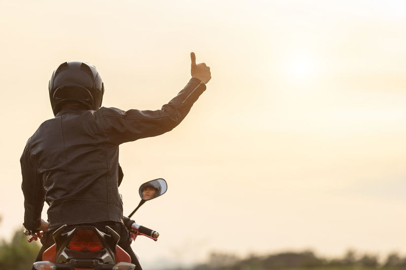 Rear view of man riding motorcycle against sky during sunset
