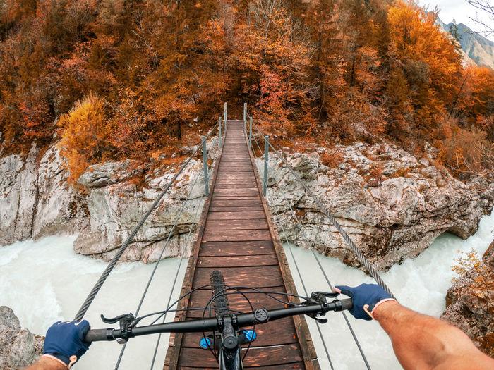 Gopro first person view mountain biking on  wooden suspension bridge above soca river, slovenia.