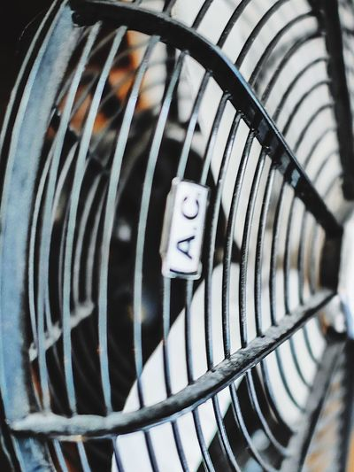 Cropped image of electric fan with text on metal grate