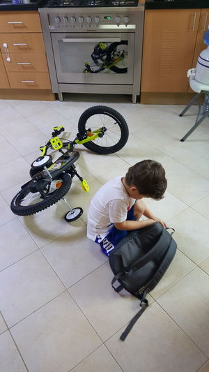 High angle view of child sitting on tiled floor