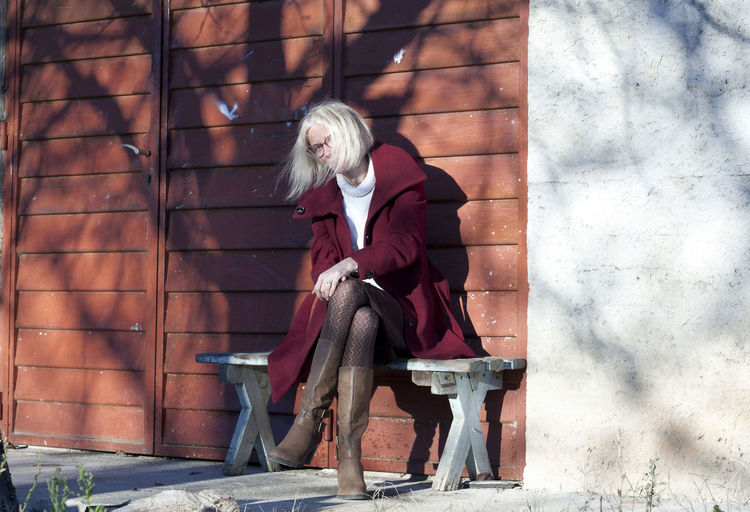 Full length of woman sitting against wall outdoors