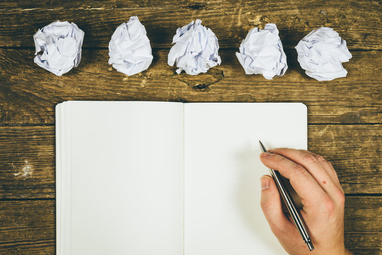 Paper Indoors  Crumpled Table Wood - Material Creativity Directly Above Crumpled Paper White Color High Angle View One Person Pen Blank Hand Human Hand Copy Space Group Of Objects Still Life Note Pad Crumpled Paper Ball Contemplation