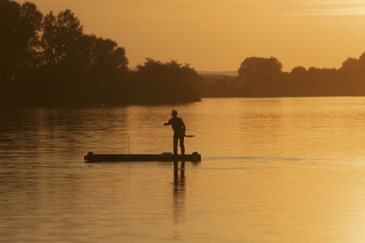 Silhouette man standing in lake against orange sky