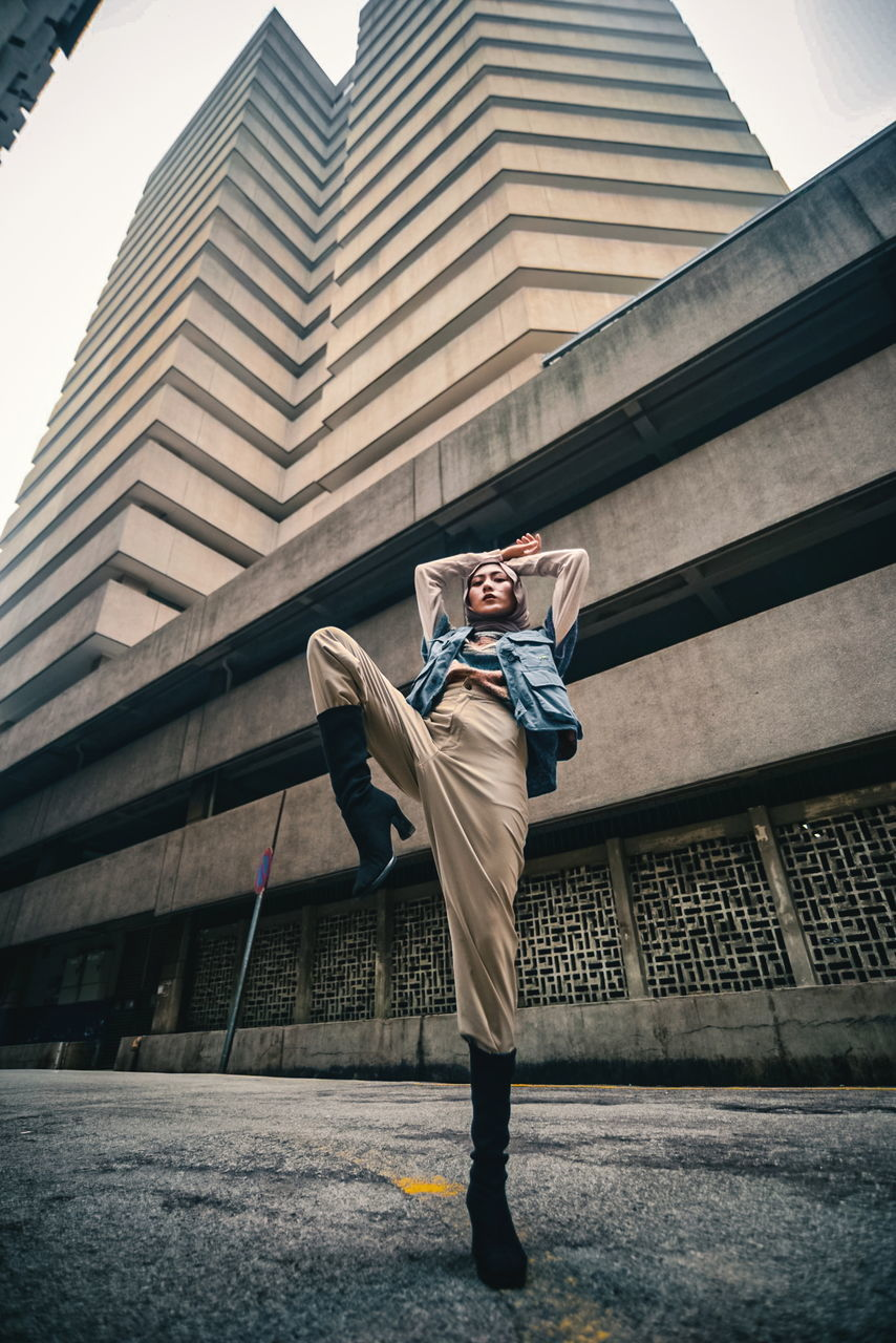 FULL LENGTH OF YOUNG MAN STANDING AGAINST BUILDINGS IN CITY