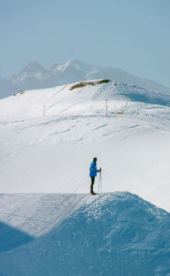 High angle view of man standing on snowcapped mountain against sky