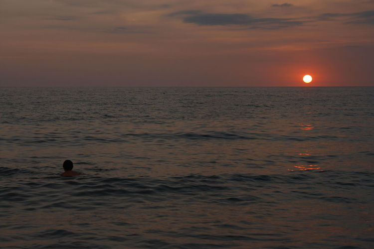 Scenic View Of Person Swimming In Calm Sea At Sunset