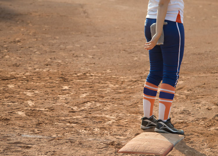 Player stand on home plate in a baseball (softball) dusty field, with copyspace Body Part Casual Clothing Day Dirt Human Body Part Human Leg Human Limb Land Leisure Activity Lifestyles Low Section Nature One Person Outdoors Real People Shoe Shorts Sport Standing Walking Women