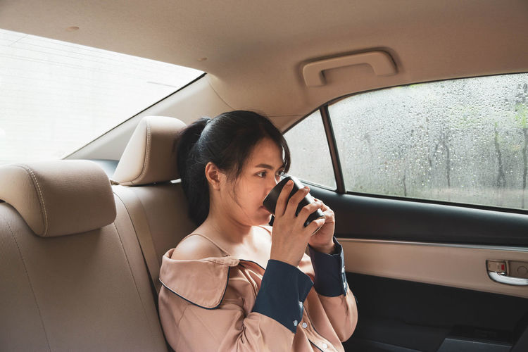 Side view of woman drinking coffee while sitting in car