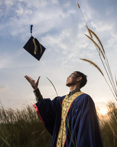 Man In Graduation Gown Standing On Field Against Sky