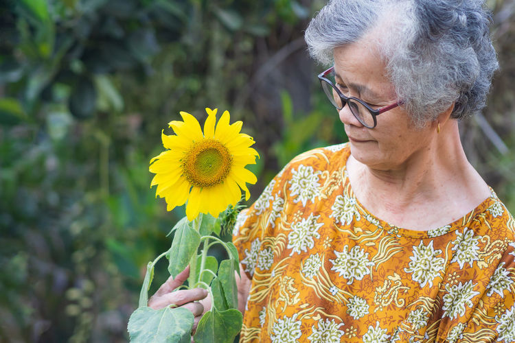 Midsection of woman holding yellow flowering plants