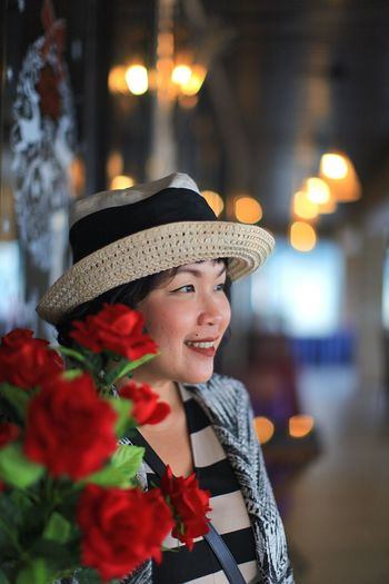 Smiling woman looking away against red flower bouquet