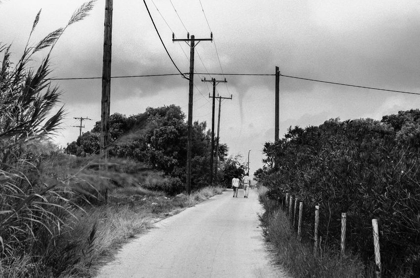 we're doomed Been There. Lost Lost In The Landscape Cable Day Electricity  Electricity Pylon Growth Men Nature One Person Outdoors People Plant Power Line  Real People Road Sky Telephone Line The Way Forward Transportation Tree Walking