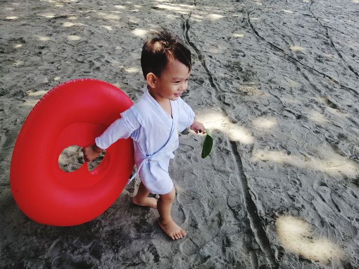 High Angle View Of Boy With Red Inflatable Ring Walking On Sand At Beach