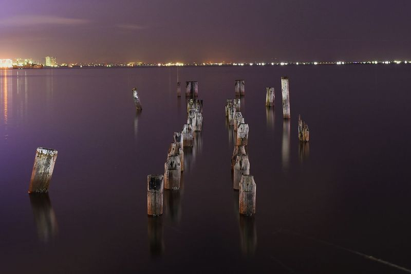 Damaged wooden posts in sea against sky at night