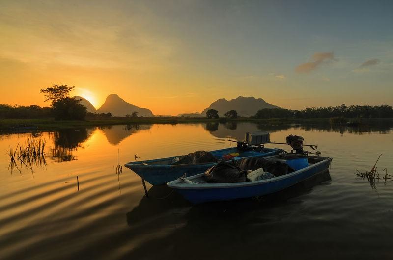 Boats Moored At Lake During Sunset