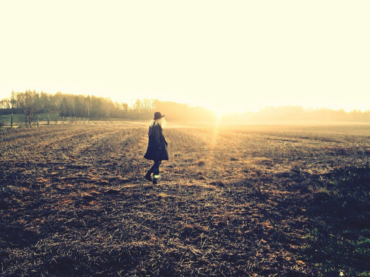 Woman walking on field during sunset