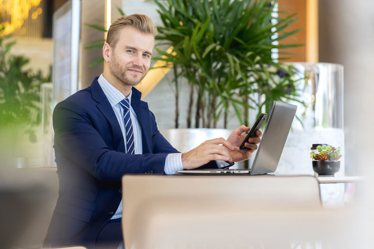 Portrait of businessman using mobile and laptop at cafe