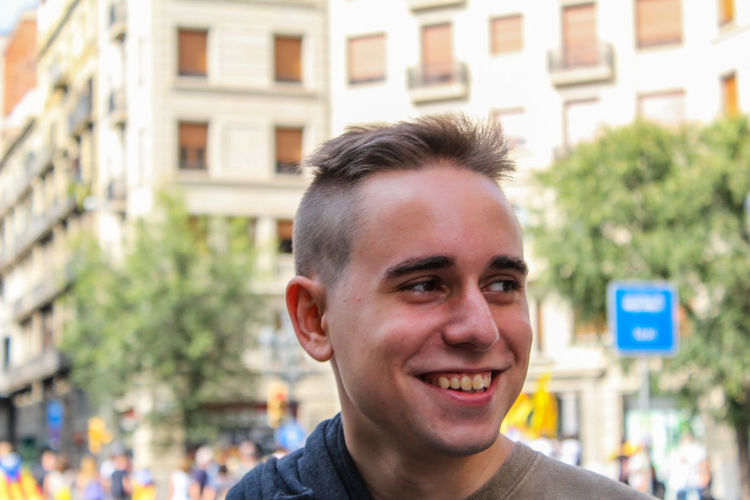 Close-Up Of Smiling Young Man Looking Away While Standing On City Street