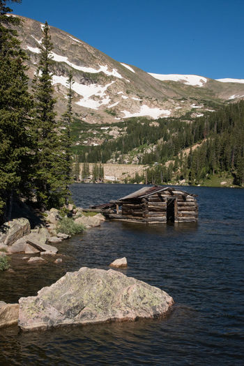 Jul 2018 - Chinn Lake, Colorado. 19th Century Cabin Granite Rocks Log Cabin Rocky Mountains USA Snow Capped Mountains Sunken Beauty In Nature Day Lake Mountain Mountain Range Nature No People Outdoors Plant Rock Rock - Object Scenics - Nature Sky Solid Tranquil Scene Tranquility Tree Water