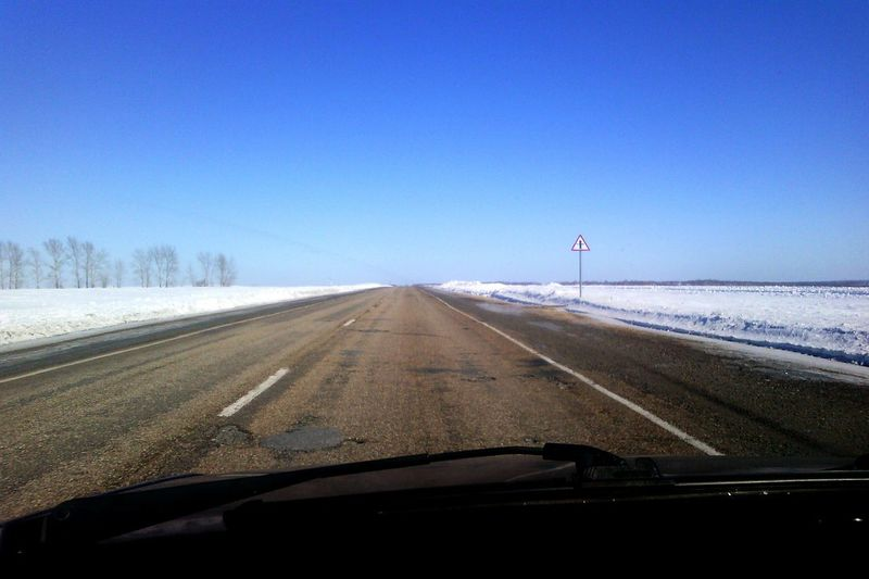 Empty road by snow covered field against clear blue sky seen through car windshield