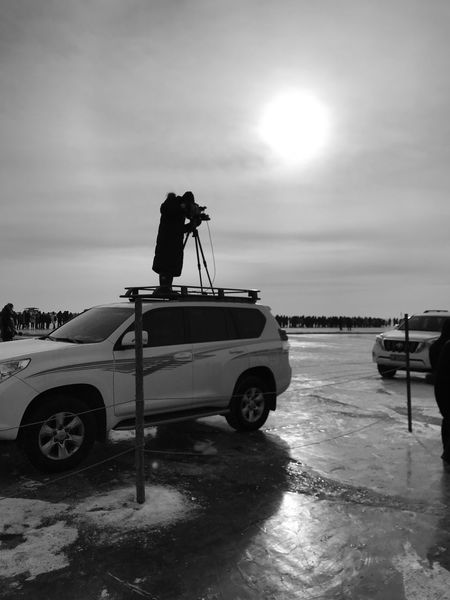 Winter fishing at Chagan Lake, Jilin, China - December 2017. A camera team of CCTV is doing a report about the traditional fishing event. Winter Fishing ᠴᠠᠭᠠᠨ ᠨᠠᠭᠤᠷ Chagan Lake 查干湖 吉林省 Lake Transportation Car Sky Mode Of Transport Real People Cloud - Sky Men