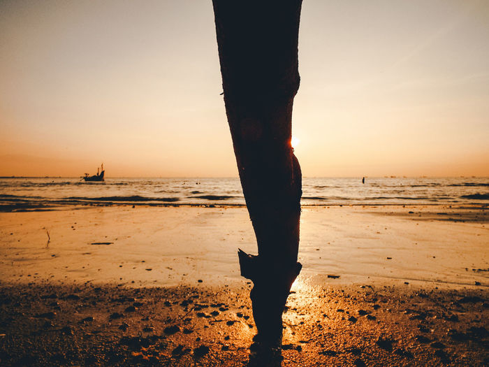 Low section of silhouette person standing on beach
