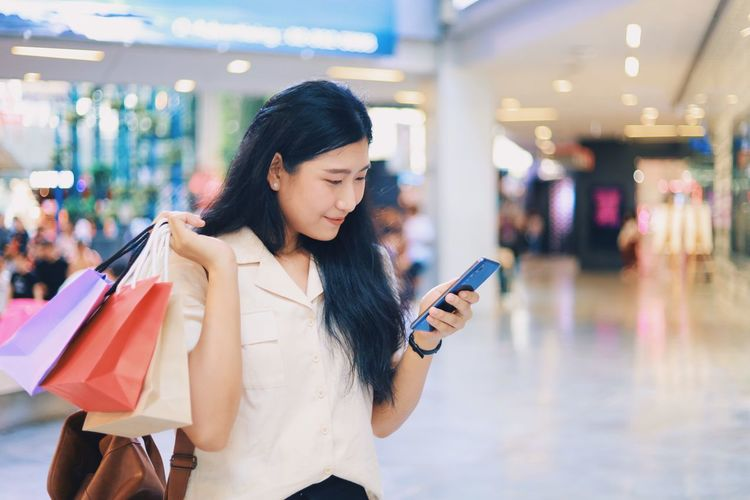 Lifestyles Bag Focus On Foreground Wireless Technology Holding Mobile Phone Women Casual Clothing Technology Leisure Activity One Person Shopping Shopping Bag Real People Hair Consumerism Connection Communication Black Hair Hairstyle Fashion Beautiful Woman
