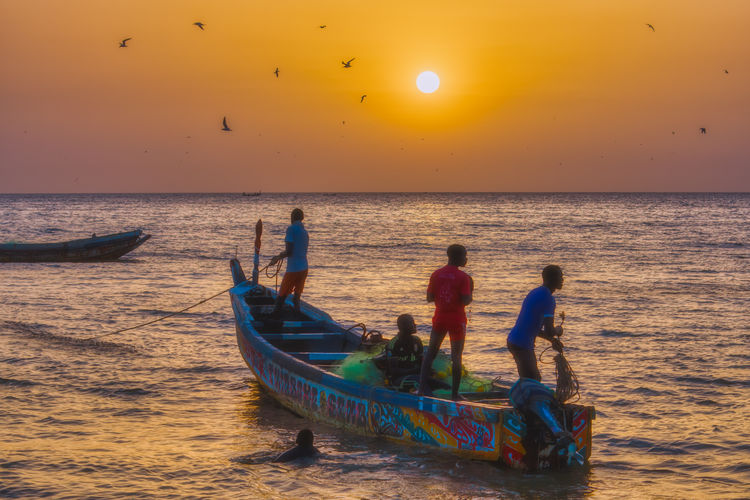 People on boat at beach during sunset