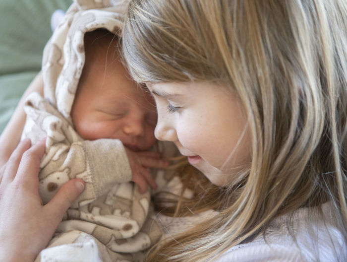 A newborn baby boy is held by his older sister on the baby's first day at home. Child Childhood Headshot Togetherness Females Two People Portrait Women Hair Innocence Girls Close-up Family Love Bonding Real People Eyes Closed  Blond Hair Cute Positive Emotion Care Hairstyle Baby Sibling Natural Light