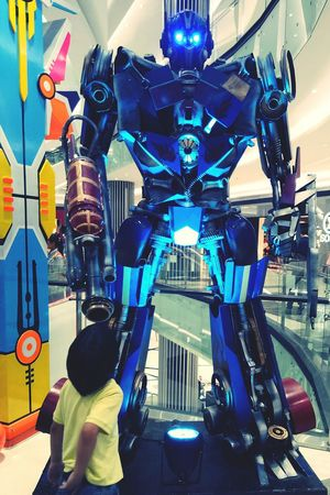 Wow! That's is how a transformer looks like David And Goliath Colorful Not Your Cliche Robot Robotics Robotsindisguise Transformers Child Kid Boy Looking Closely Built Structure Indoors  Low Angle View Architecture Day Close-up City
