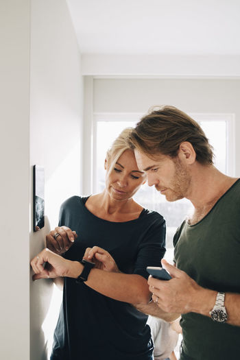 Couple holding mobile phone while standing on wall