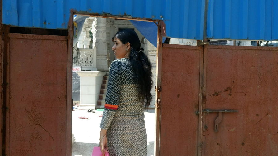 Rear View Of Woman Entering From Metallic Gate