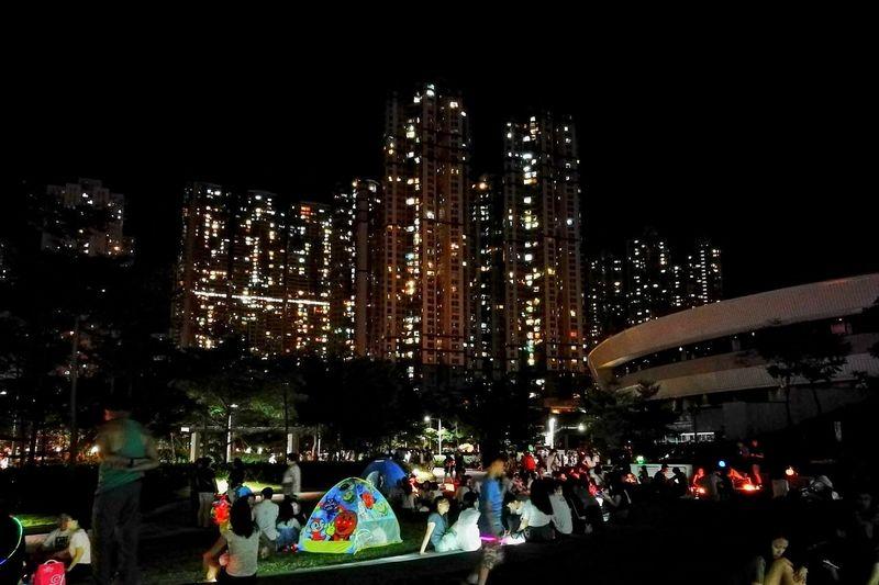 People on illuminated city buildings at night