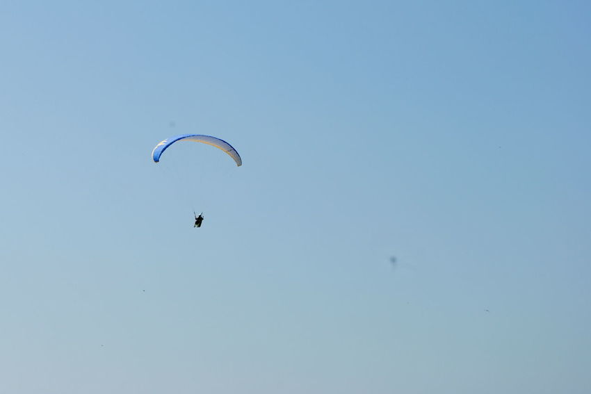 Adventure Beauty In Nature Blue Day Extreme Sports Flying Freedom Fun Hot Air Balloon Leisure Activity Lifestyles Low Angle View Mid-air Multi Colored Nature Outdoors Parachute Paragliding Scenics Sky Sport Tranquil Scene Tranquility Unrecognizable Person