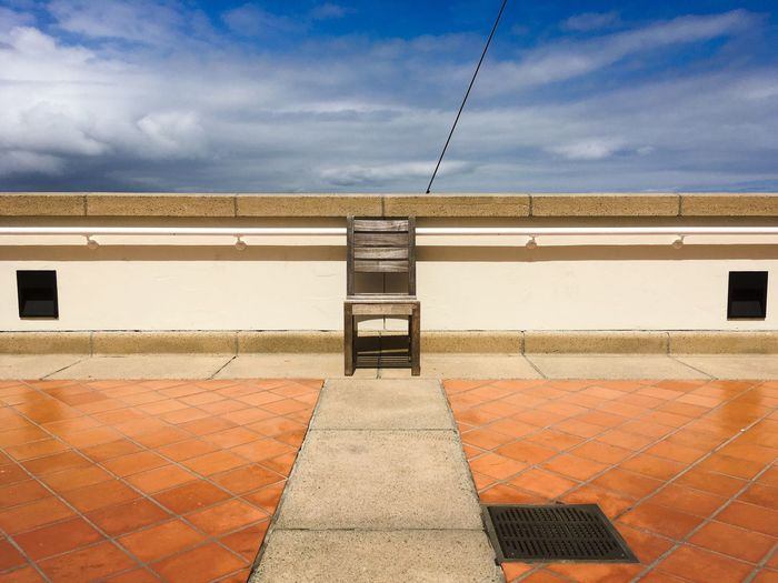Wooden Chair On Promenade Against Sky