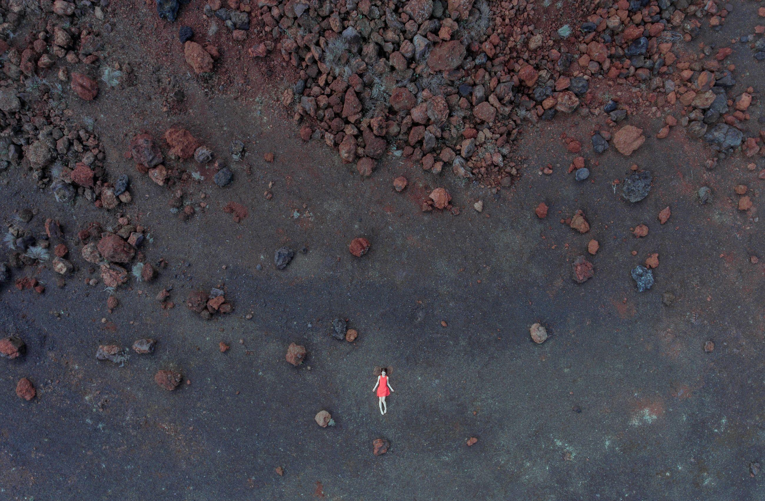 HIGH ANGLE VIEW OF WOMAN STANDING ON SAND