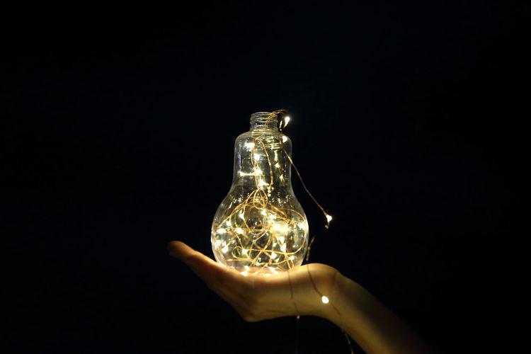 Close-up of illuminated light bulb over black background