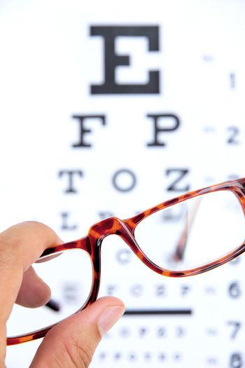 Cropped hand holding eyeglasses against eye chart